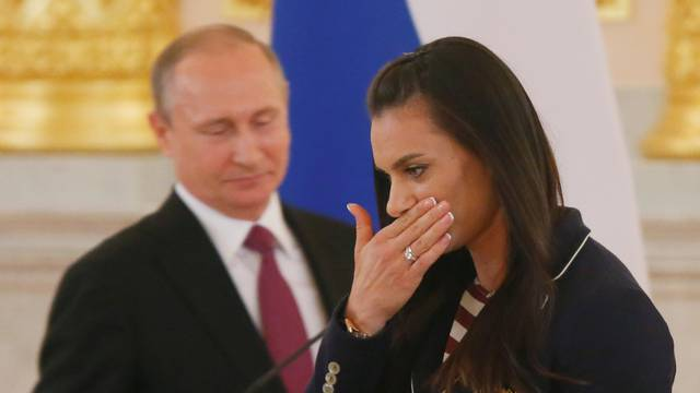 Track-and-field athlete Isinbayeva reacts as she walks past Russian President Putin during his personal send-off for members of the Russian Olympic team at the Kremlin in Moscow