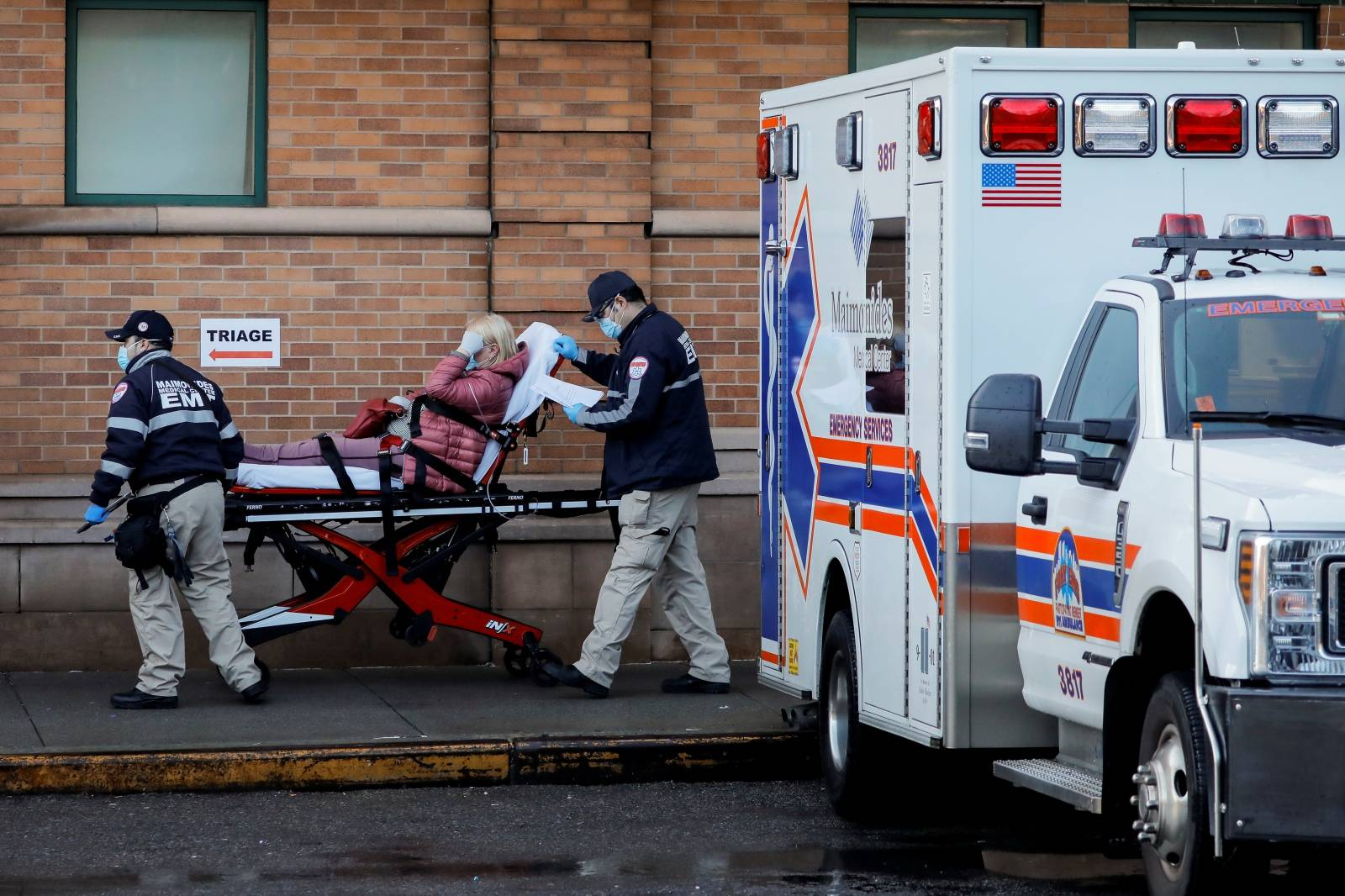 Paramedics take a patient in to an emergency center at Maimonides Medical Center during the outbreak of the coronavirus disease (COVID-19) in the Brooklyn, New York