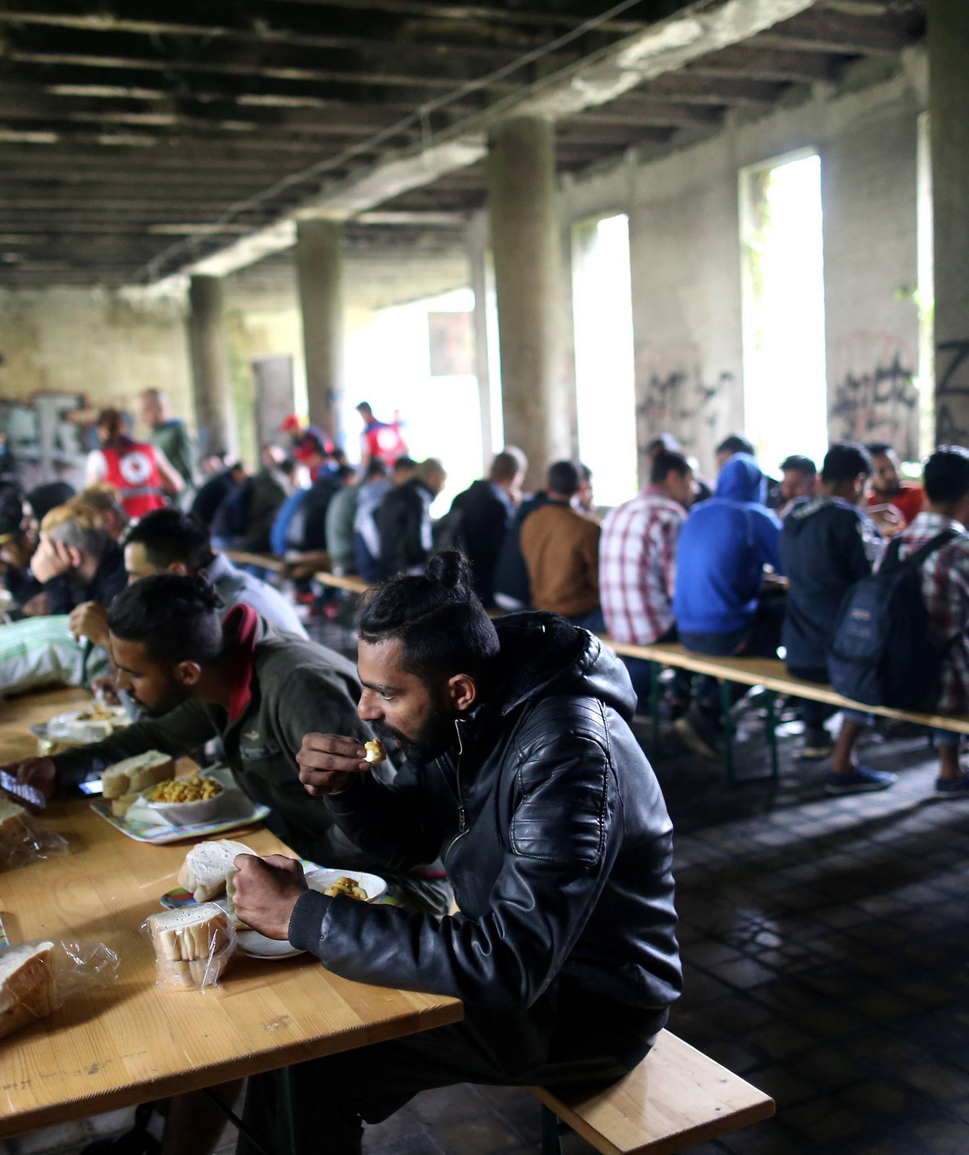 Migrants eat in a dorm destroyed during the Bosnian 1992-1995 war, in Bihac