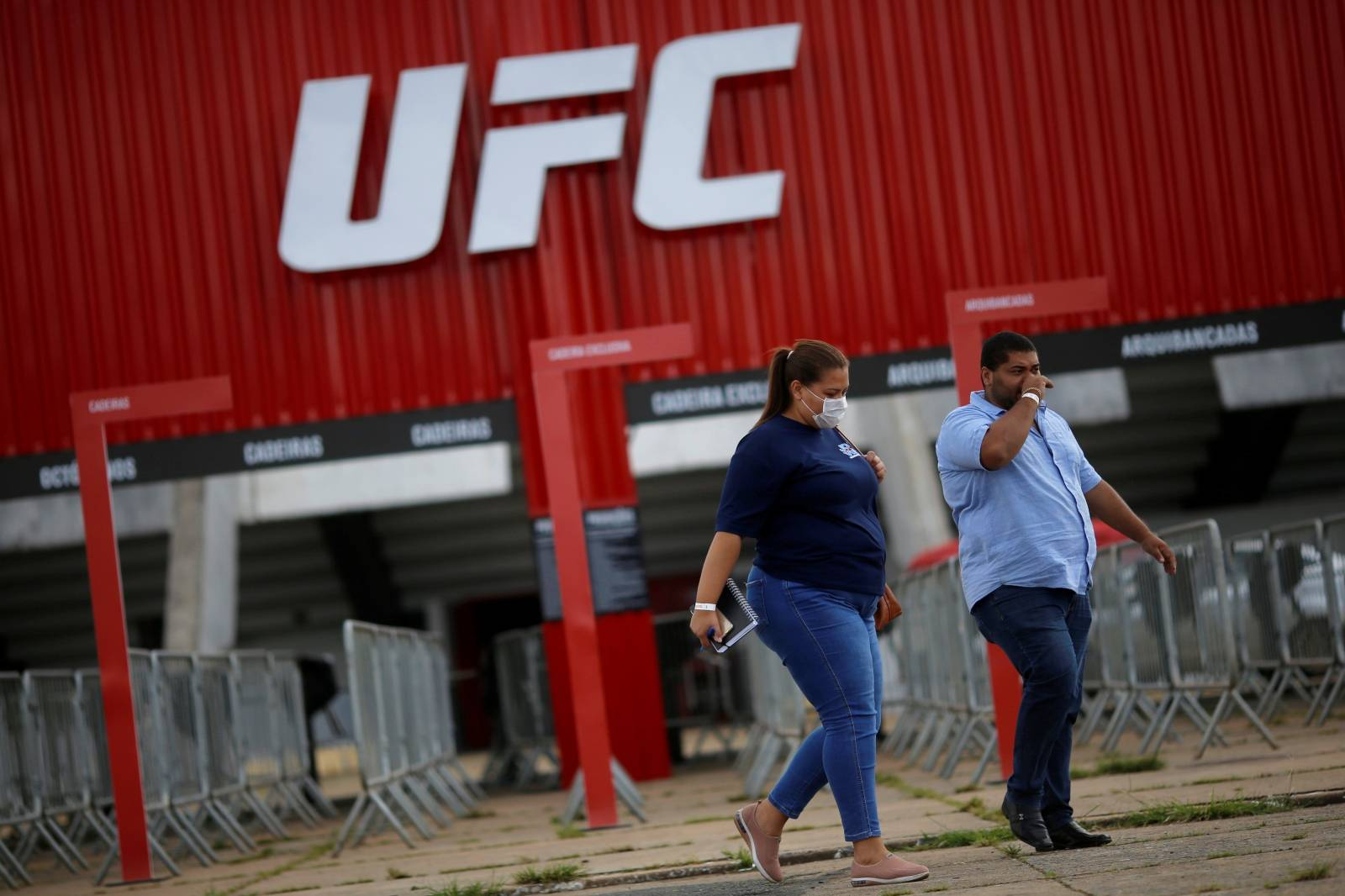 A woman wears a protective face mask in front of the Nilson Nelson Gymnasium as the next UFC Fight Night will be held without fans during the fights, after reports of the coronavirus in Brasilia