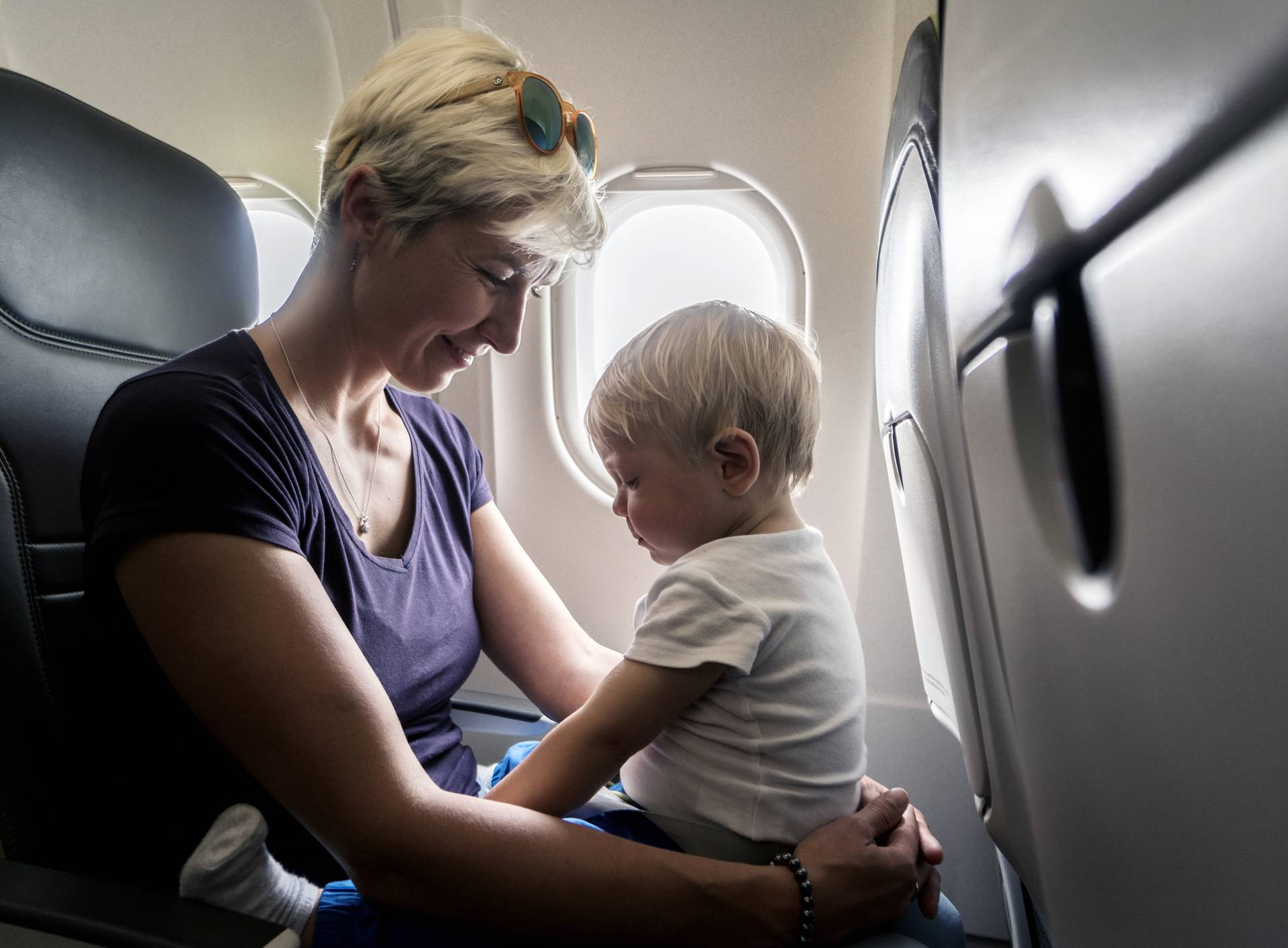 Mom spending time with her one year old baby boy during flight