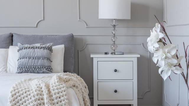 Simple white lamp on wooden night stand table with two drawers n