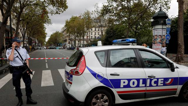 French police secure the area next to a church during a security operation in a shopping district of Paris