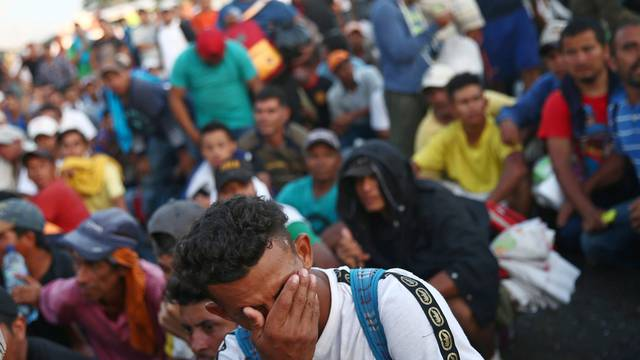A Central American migrant, part of a caravan trying to reach the U.S., gestures as he waits on the bridge that connects Mexico and Guatemala to cross into Mexico to continue his trip, in Ciudad Hidalgo