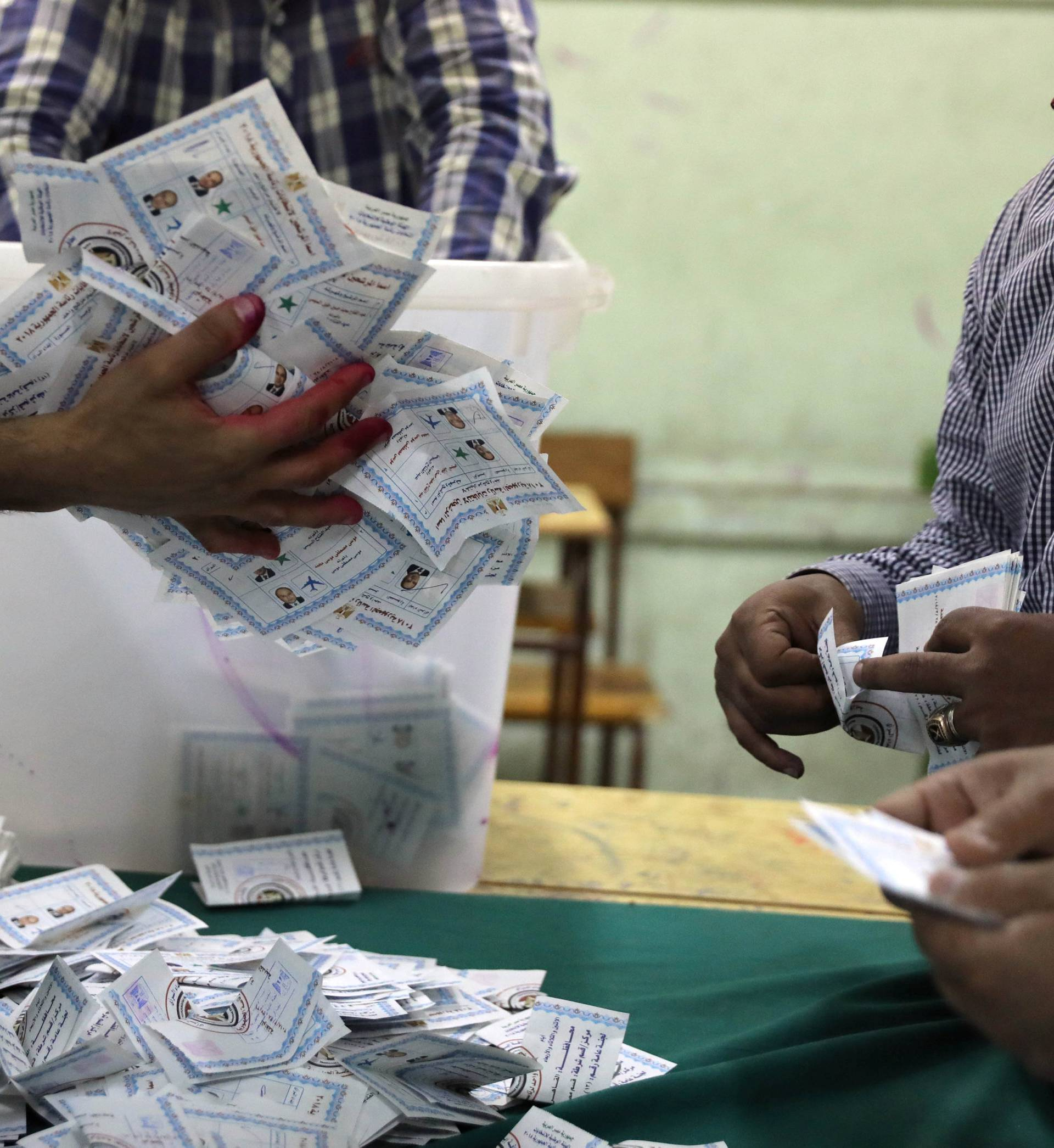 Electoral workers sort ballots to count votes after polls closed during the presidential election in Cairo