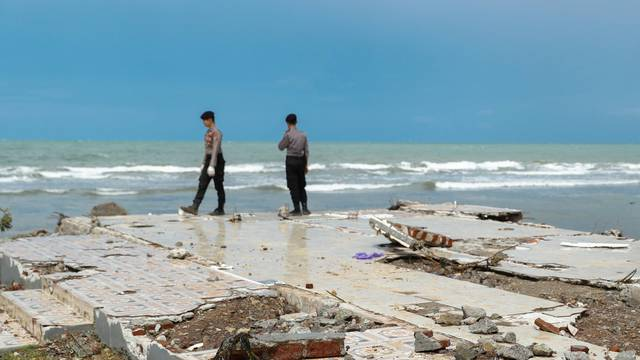 Police officers search for victims among rubble of a destroyed beach front hotel which was hit by a tsunami in Pandeglang