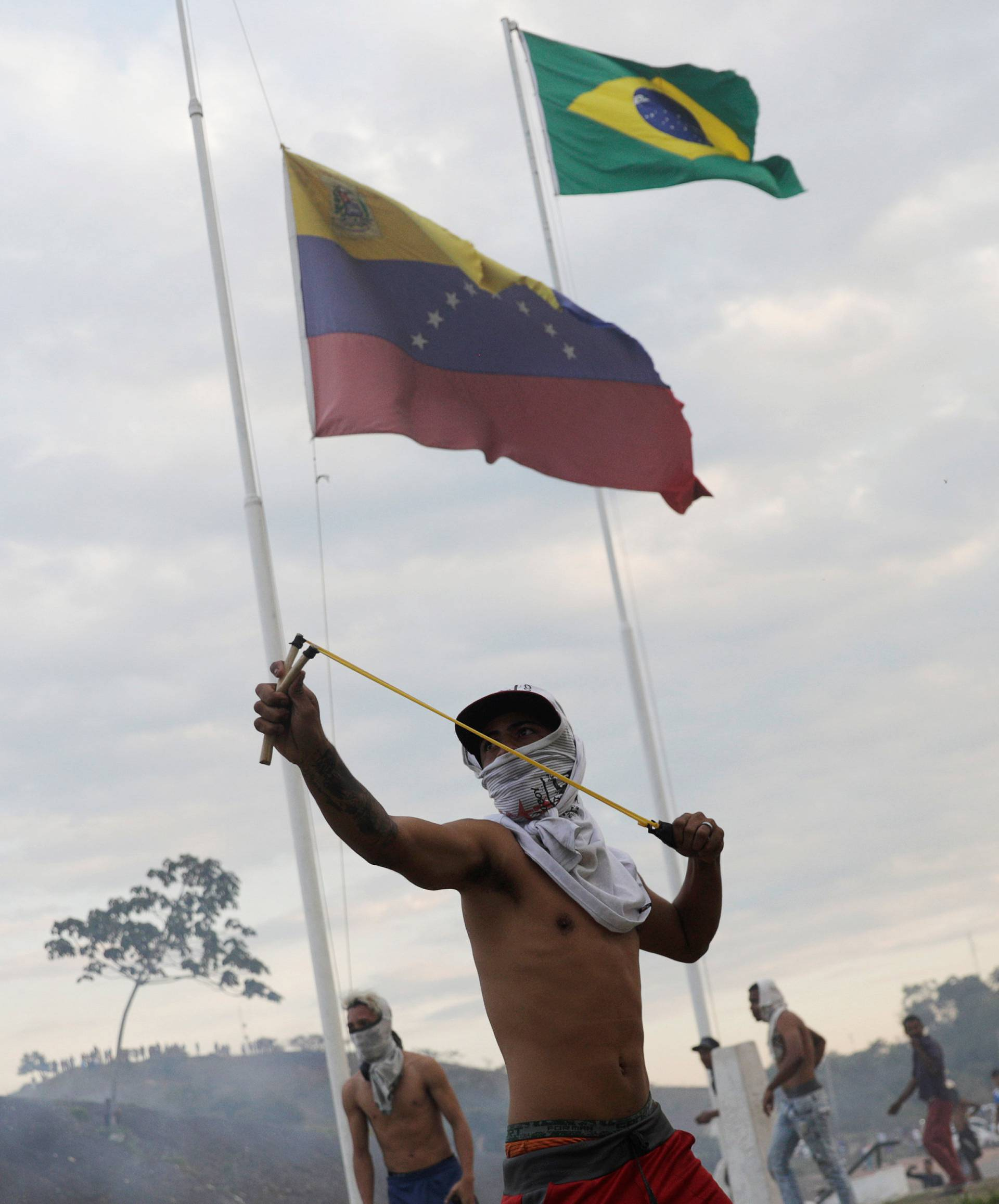 A protester uses a slingshot during clashes with Venezuelan soldiers along the border between Venezuela and Brazil in Pacaraima