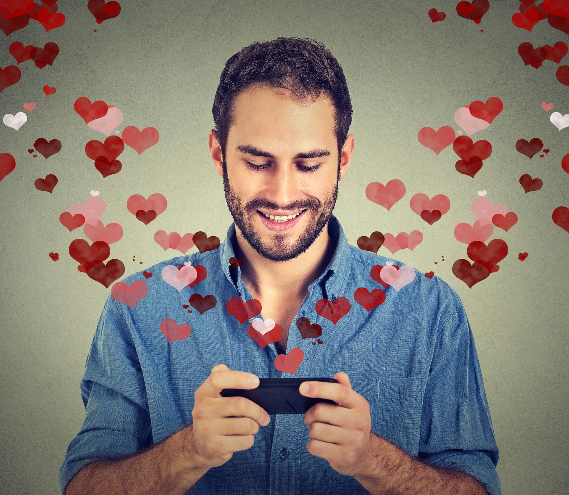 man sending love sms message on mobile phone with hearts flying away