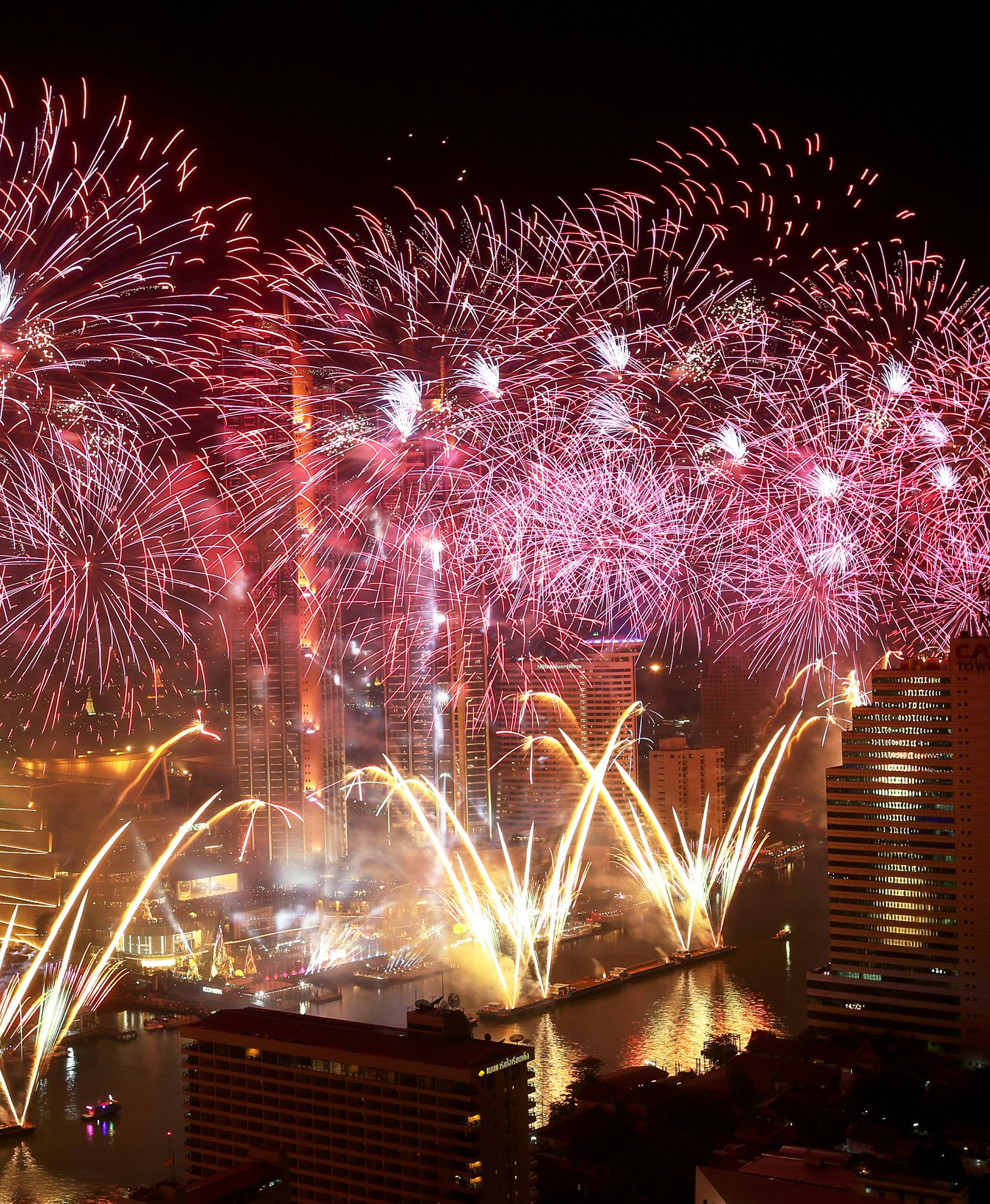 Fireworks explode over Chao Phraya River during the New Year celebrations in Bangkok