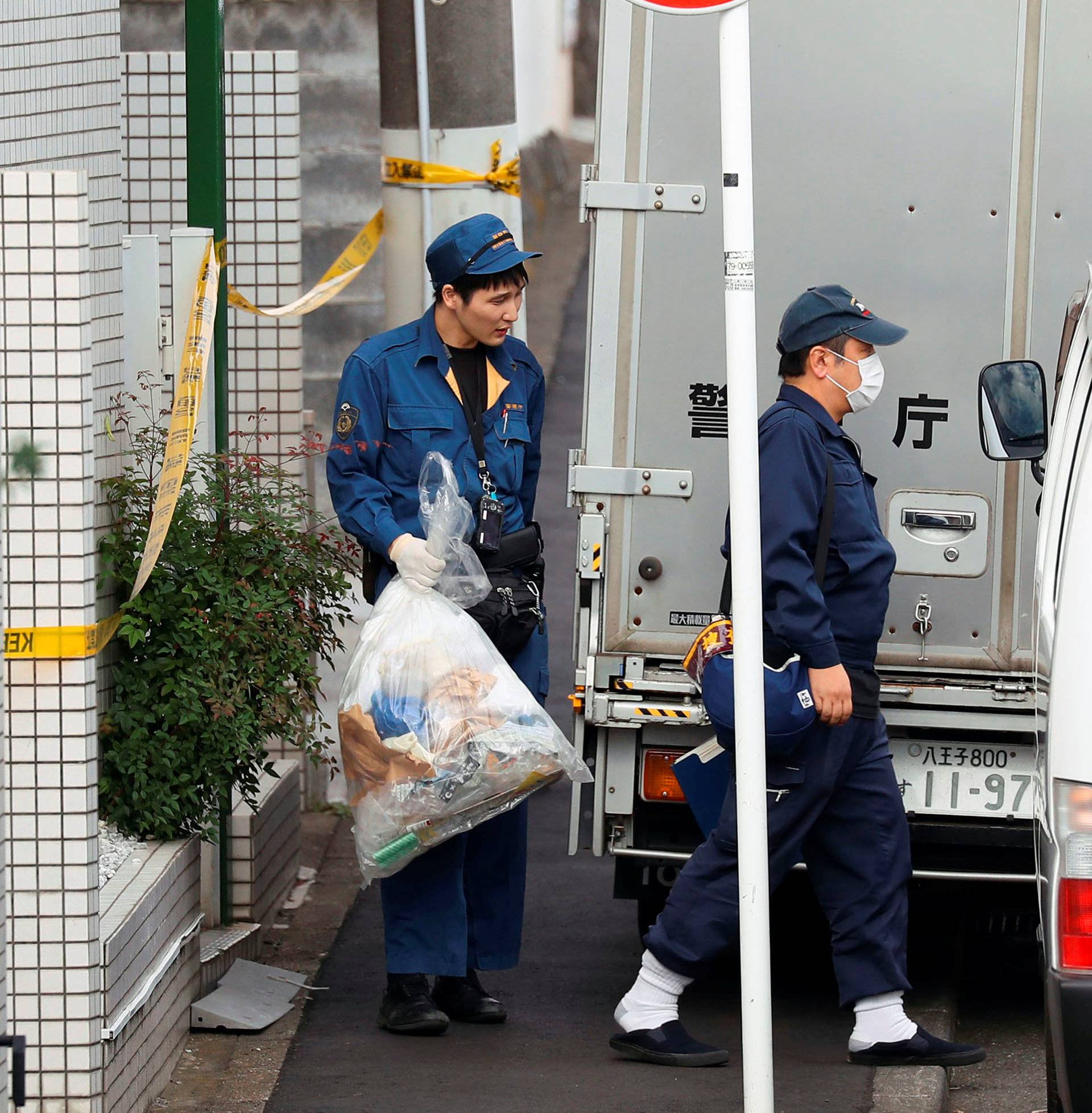 Police officer carries out a plastic bag from an apartment building where media reported nine bodies were found in Zama