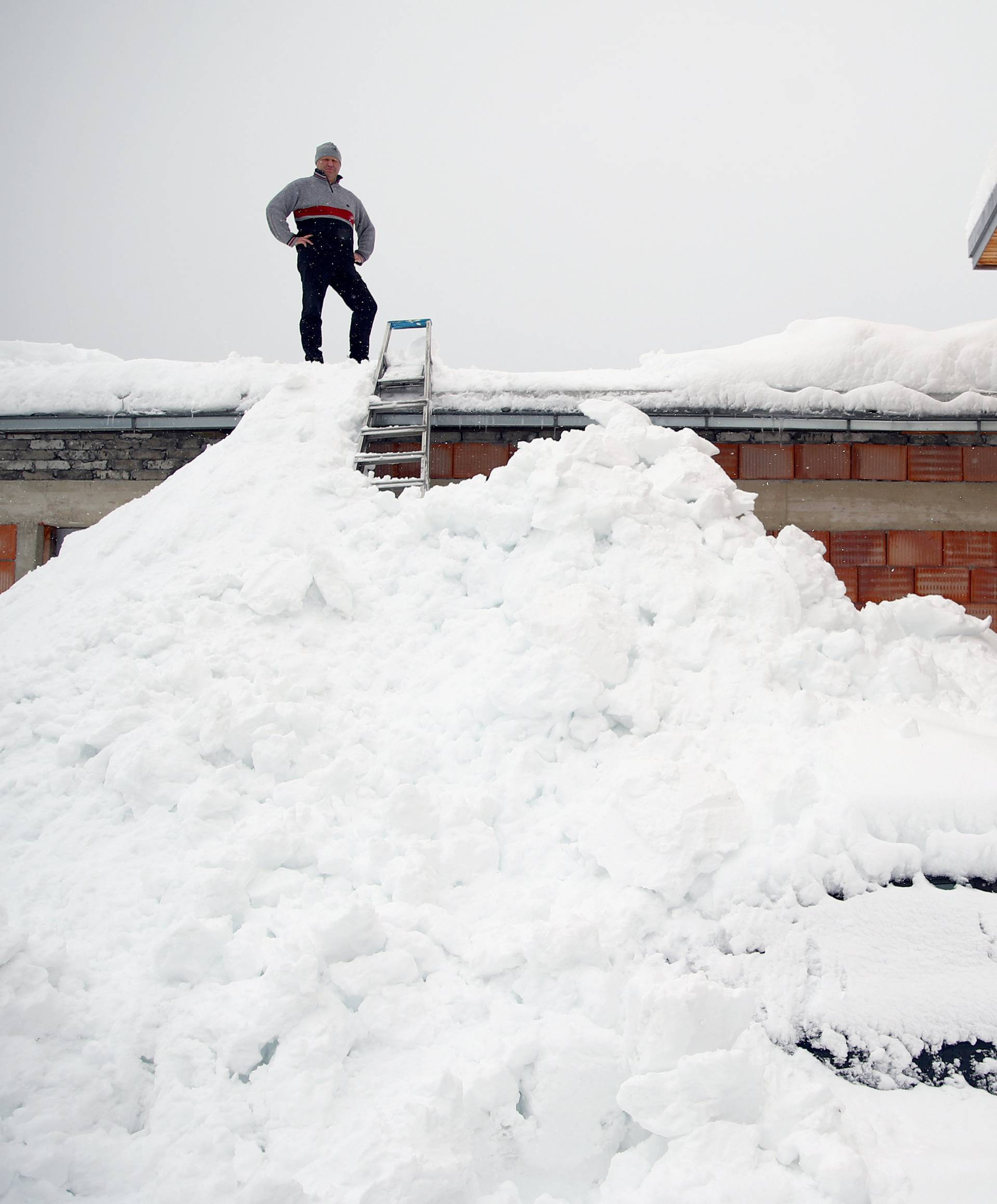 Gottfried Klapfer stands on the rooftop of his company's building during heavy snowfall in Eisenerz