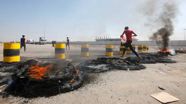 Iraqi protesters burn tires as they block the entrance of Umm Qasr Port south of Basra