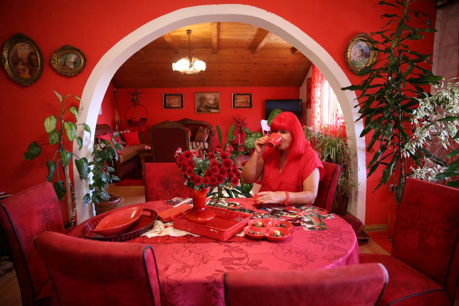 Zorica Rebernik, obsessed with the red color, drinks coffee in her house in the village of Breze near Tuzla