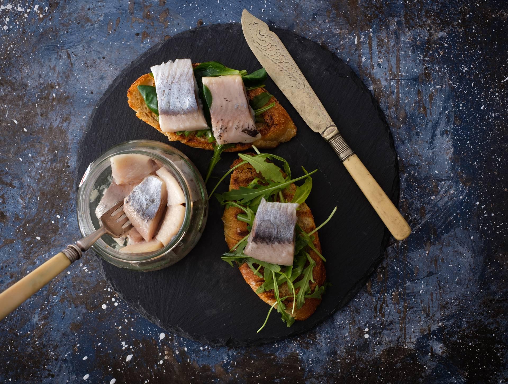 Herring sandwich (traditional Danish smorrebrod) on cutting boar