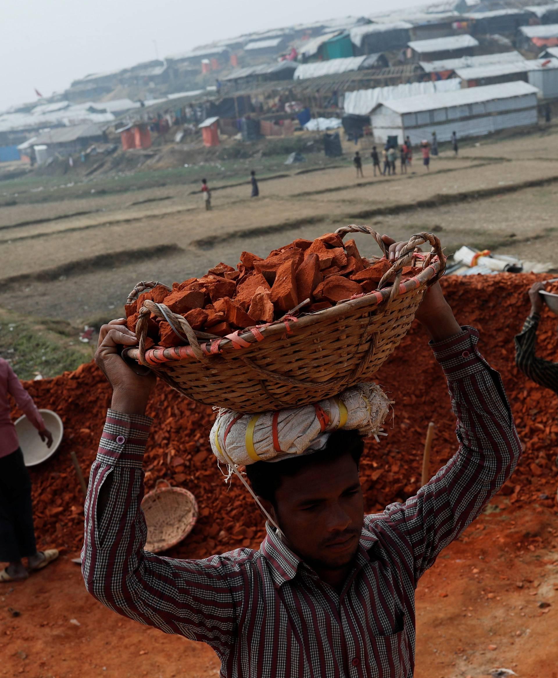 Rohingya refugees carry bricks at Palong Khali camp, near Cox's Bazar