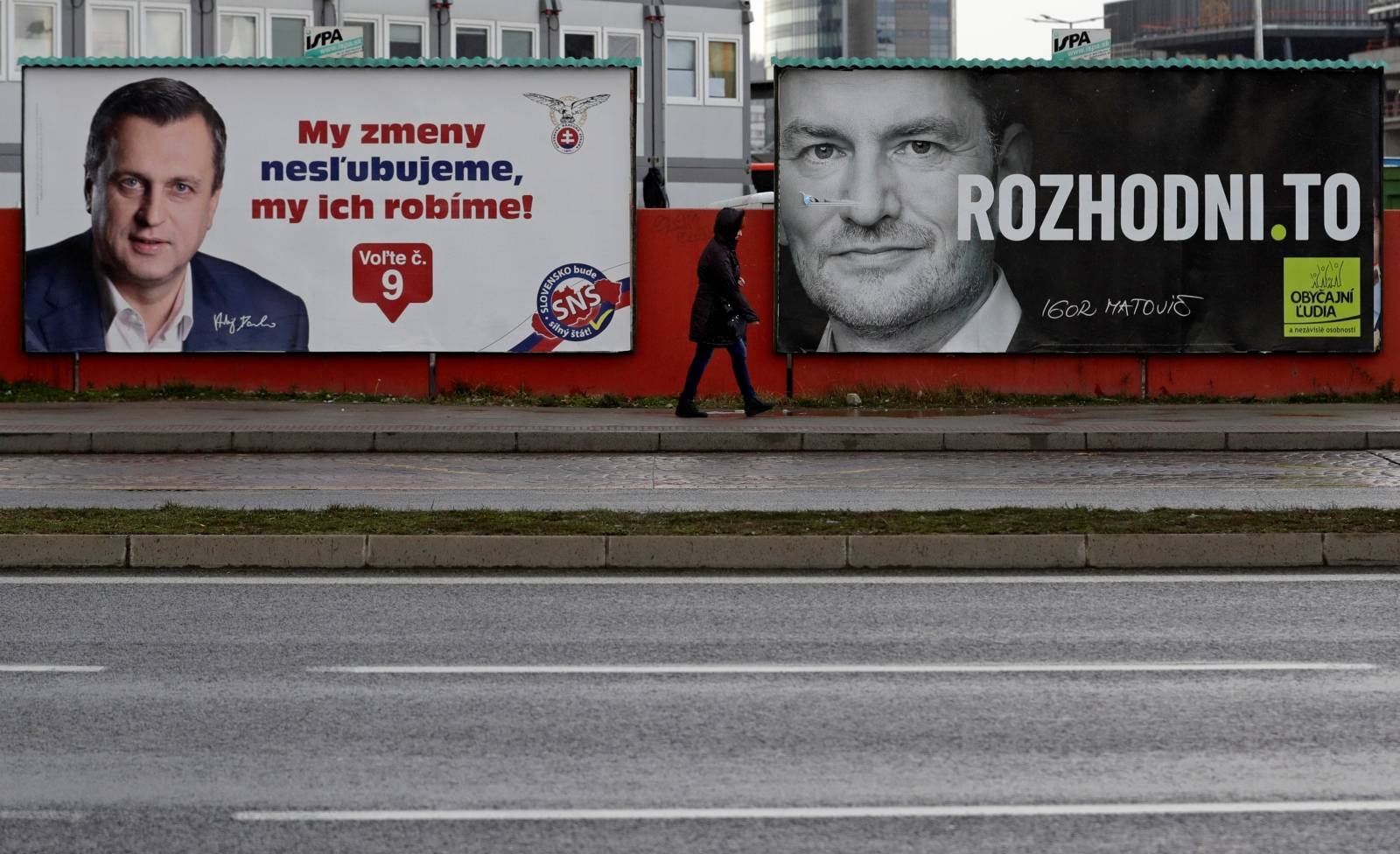 Woman walks past election posters ahead of country's parliamentary election in Bratislava