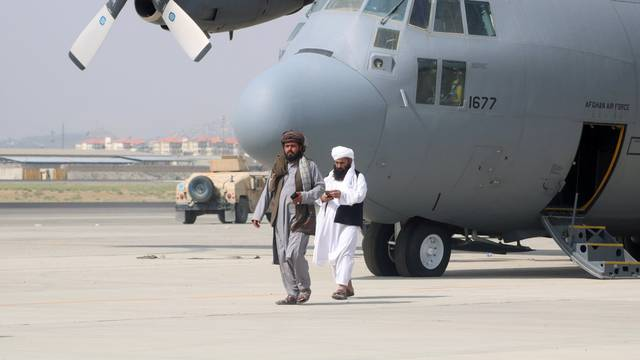 Taliban walk in front of a military airplane a day after the U.S. troops withdrawal from Hamid Karzai international airport n Kabul