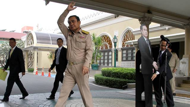 Thailand's Prime Minster Prayuth Chan-ocha waves to reporters next to a cardboard cut-out of himself at the government house in Bangkok