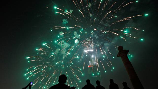 People gather to observe fireworks in celebration of the New Year in Karachi