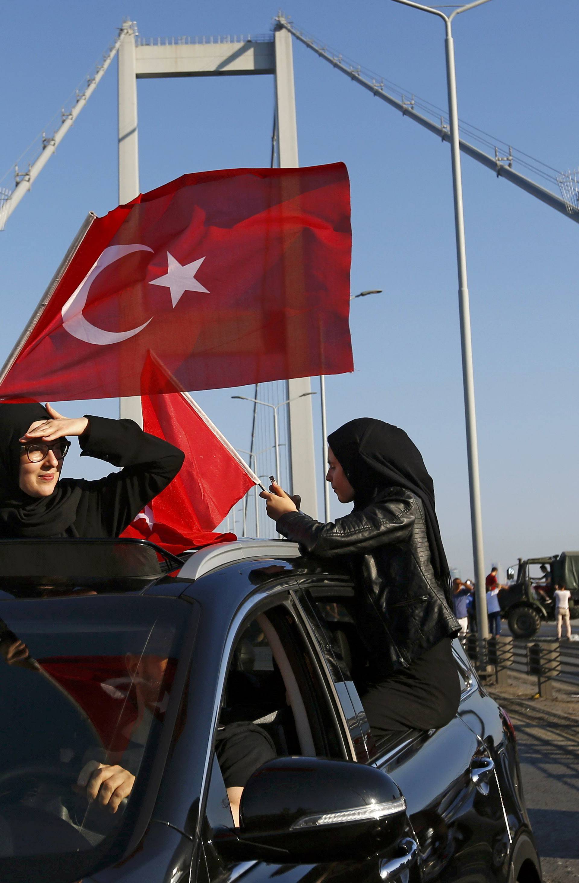 Women wave Turkish flags after troops involved in the coup surrendered on the Bosphorus Bridge in Istanbul