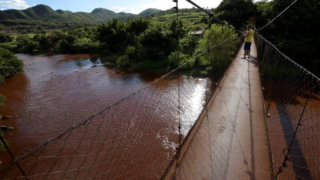 Residents stand on a bridge over mud-filled Paraopeba river, after a tailings dam owned by Brazilian mining company Vale SA collapsed, in Mario Campos near Brumadinho