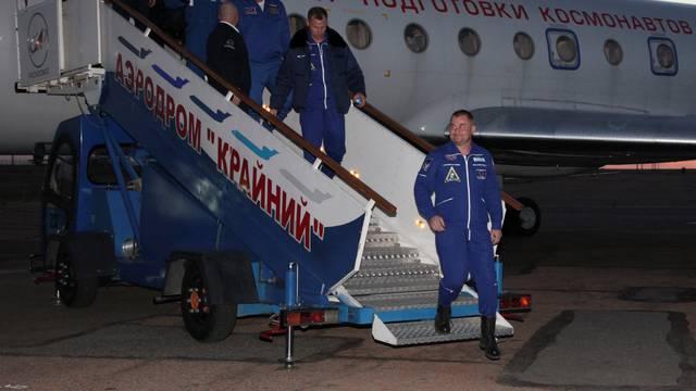 Russian cosmonaut Ovchinin and U.S. astronaut Hague arrive at Baikonur airport