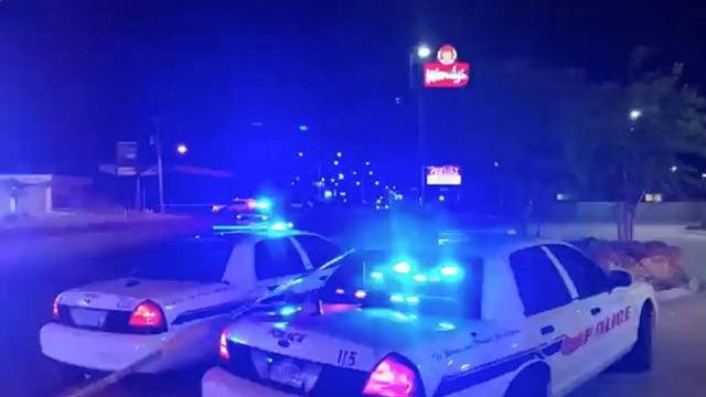 Police vehicles are seen near the scene in the aftermath of a drive-by shooting at a liquor store in Shreveport, Louisiana