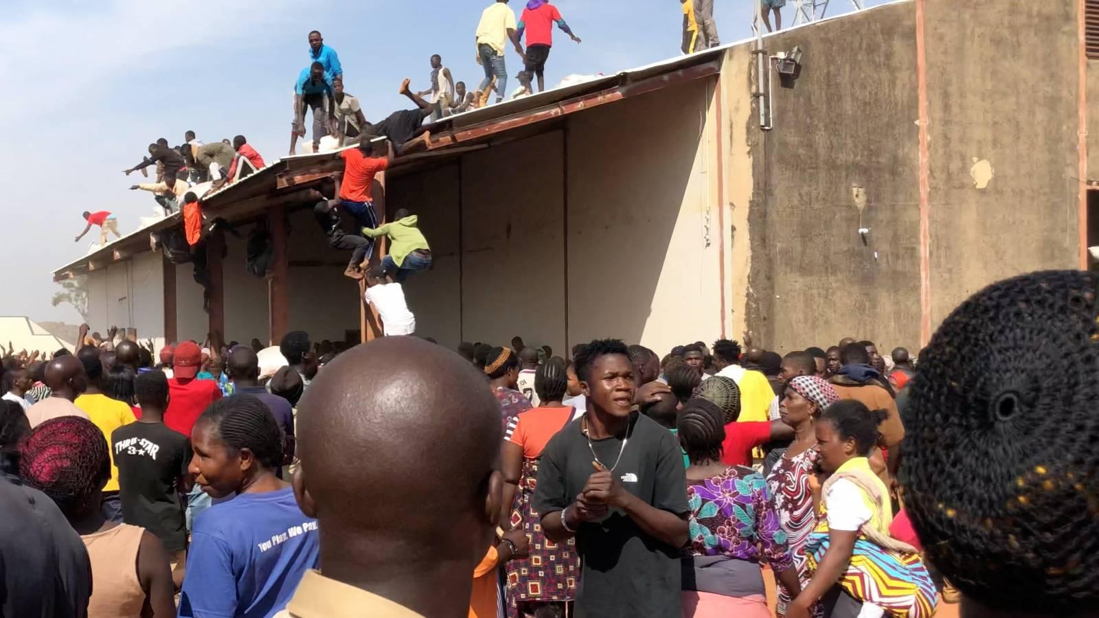 People gather around a warehouse in Bukuru