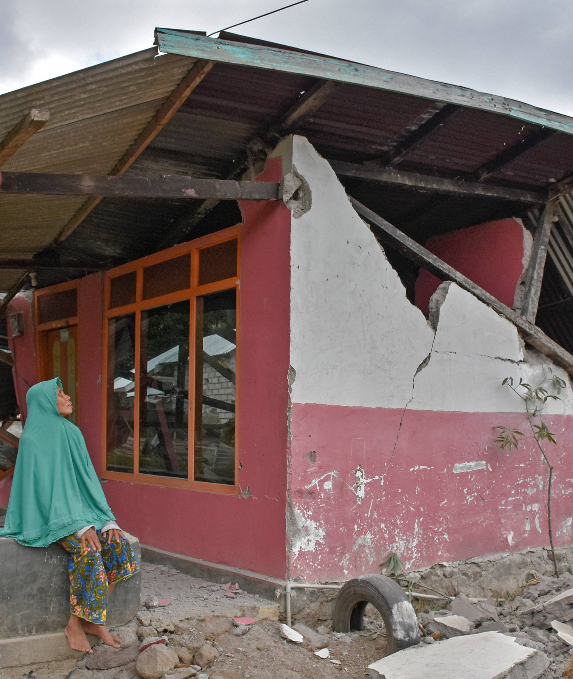 A villager sits at her damaged house after an earthquake hit Sembalun Bumbung village in Lombok Timur