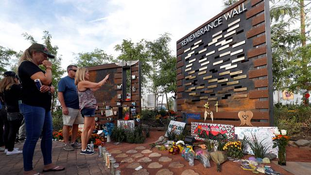 People look over a Remembrance Wall at the Las Vegas Healing Garden during the one-year anniversary of the October 1 mass shooting in Las Vegas