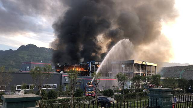 Rescue workers try to put out a fire after an explosion at a chemical plant inside an industrial park in Yibin, Sichuan