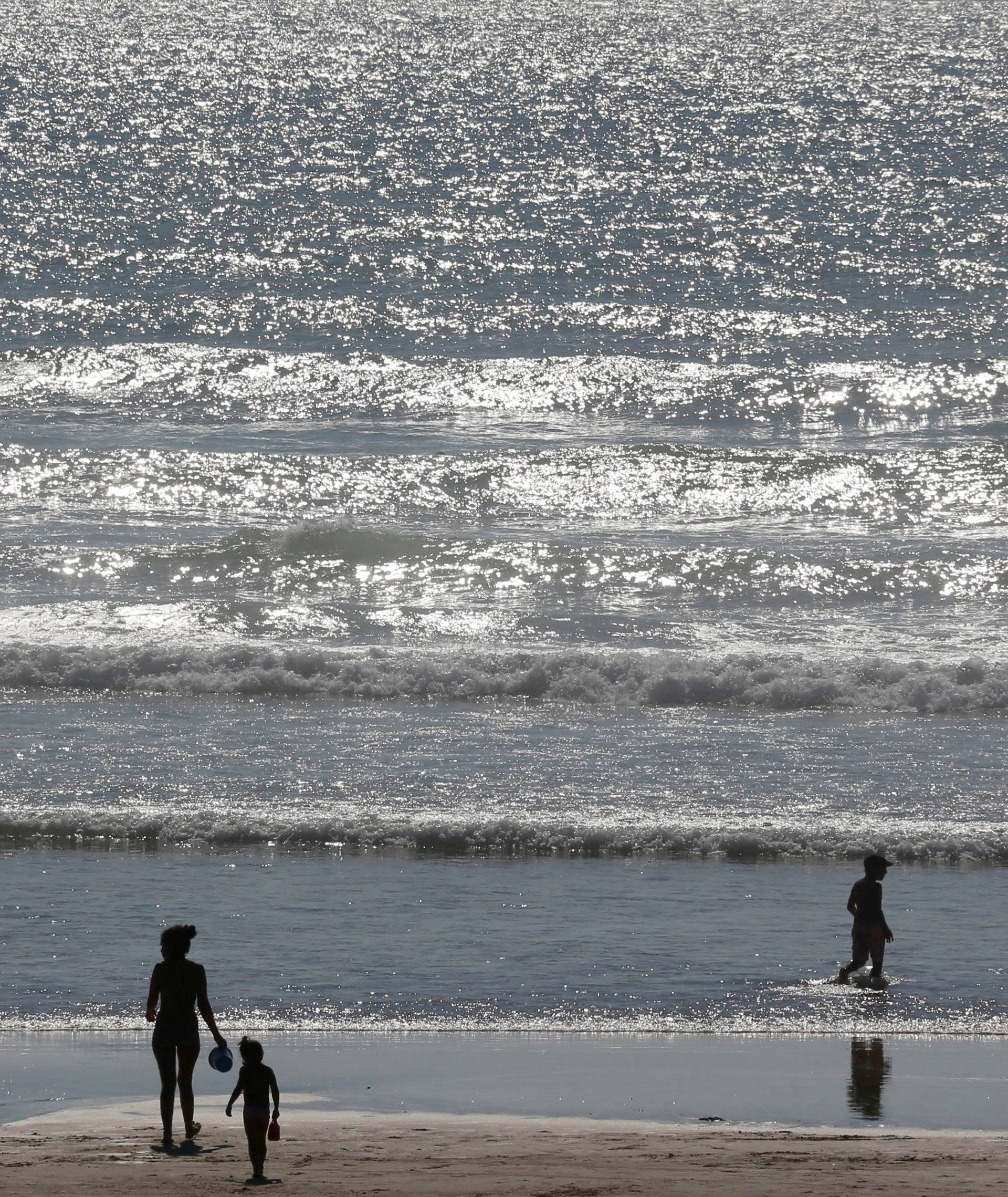 Holidays makers walk on the beach along the Atlantic Ocean as warm summer temperatures continue in Montalivet