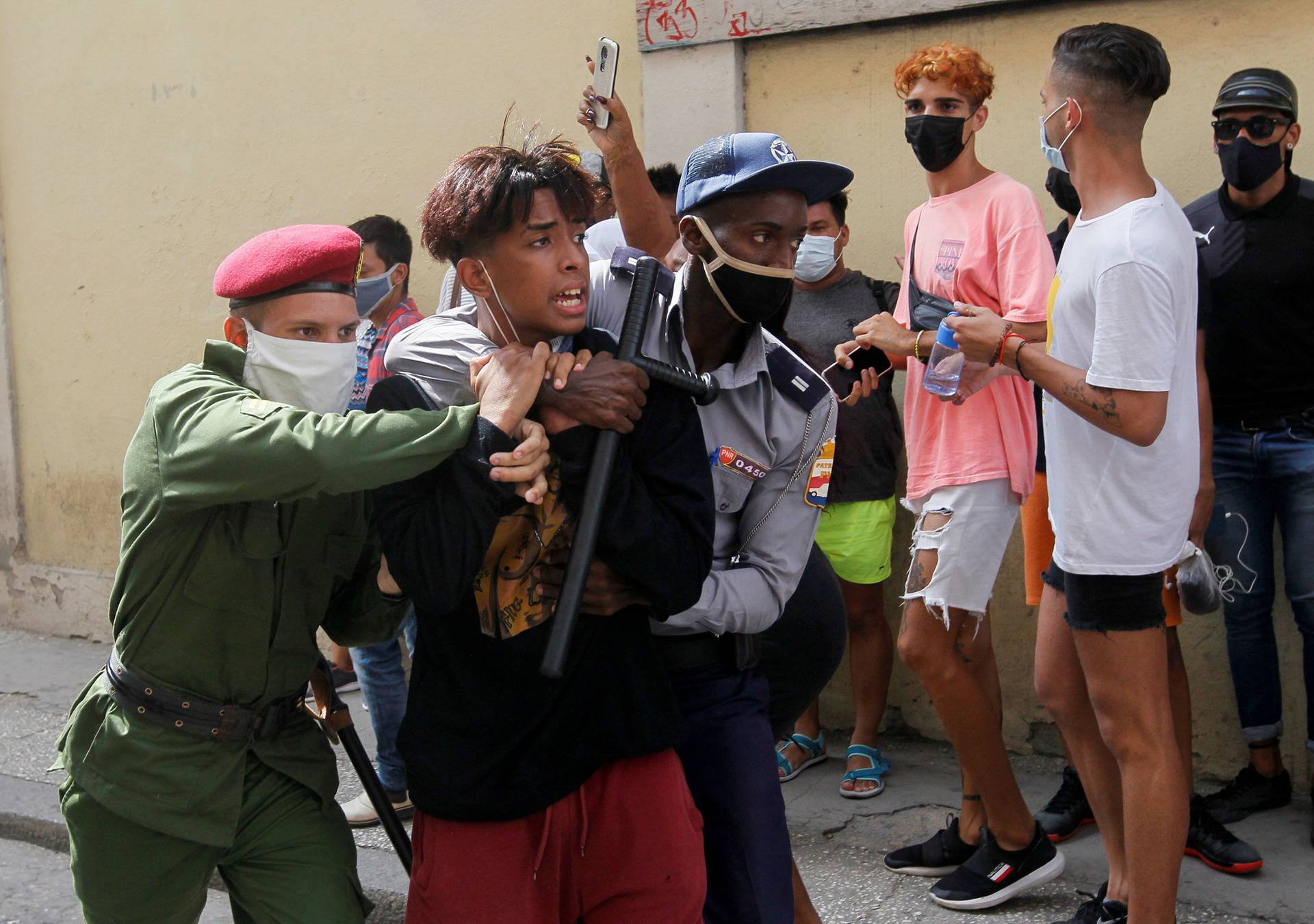 Police detain a person during protests against and in support of the government, in Havana