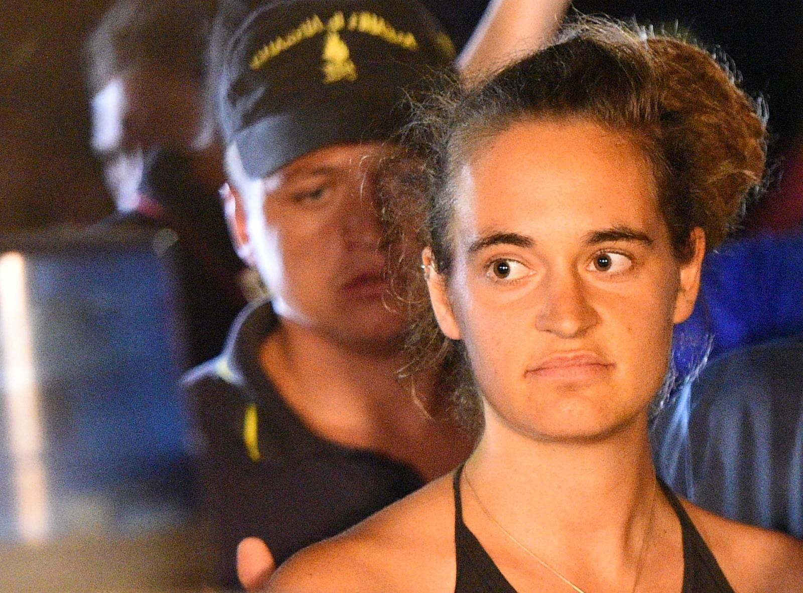 Sea-Watch 3 captain Carola Rackete is escorted off the ship by police and taken away for questioning, in Lampedusa