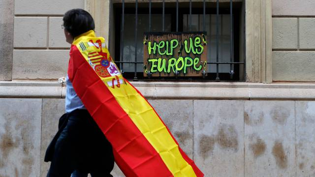 Pro-union supporters walk past a home made appeal for help during a demonstration in a square in Sabadell, Calatonia