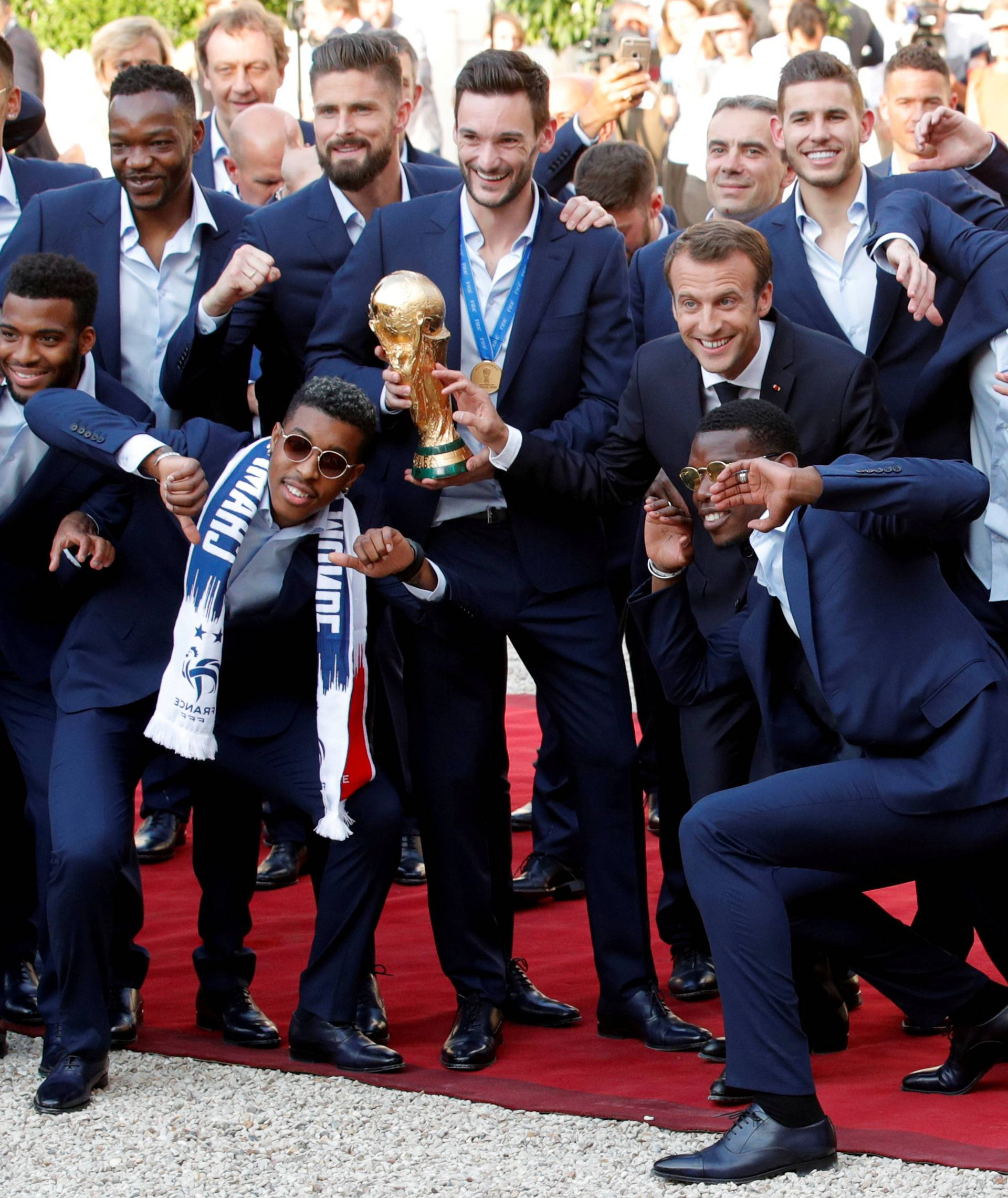 French President Emmanuel Macron and his wife Brigitte Macron pose with France soccer team captain Hugo Lloris holding the trophy, coach Didier Deschamps and players before a reception to honour the France soccer team at the Elysee Palace in Paris