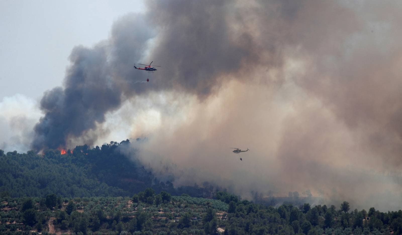 Helicopters drop water over a forest fire near Bovera