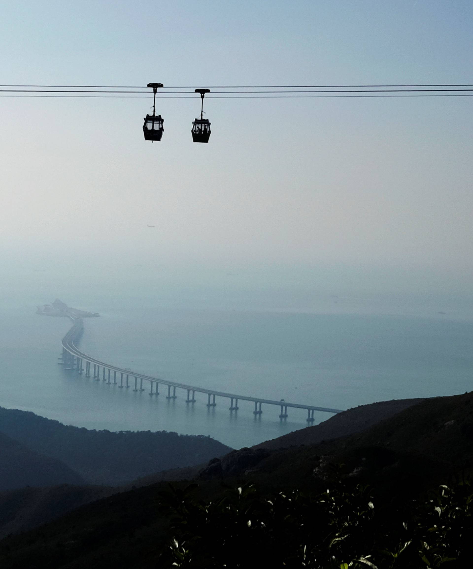 Cable cars move in front of the Hong Kong-Zhuhai-Macau bridge off Lantau island in Hong Kong
