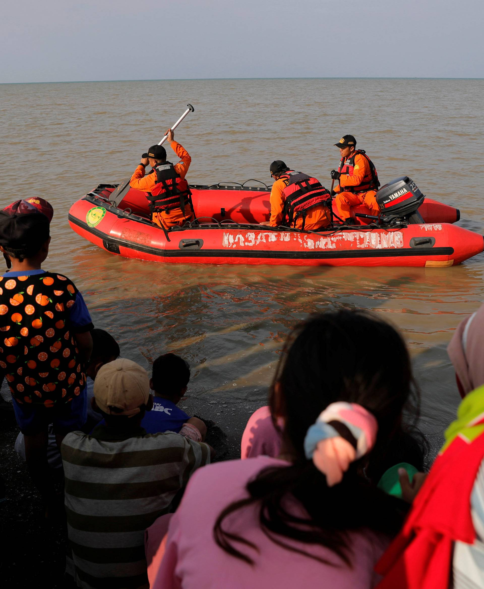 People watch rescue team members prepare the boat heading to the Lion Air, flight JT610, sea crash site off the coast of Karawang regency