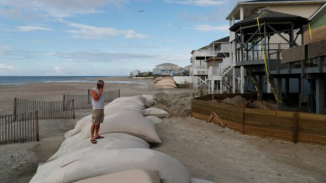 Dennis Kernodle talks on the phone during storm preparations of his oceanfront home ahead of the arrival of Hurricane Florence in Ocean Isle Beach