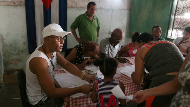 Election officials check the documents of a voter at a polling station during a constitutional referendum in Havana