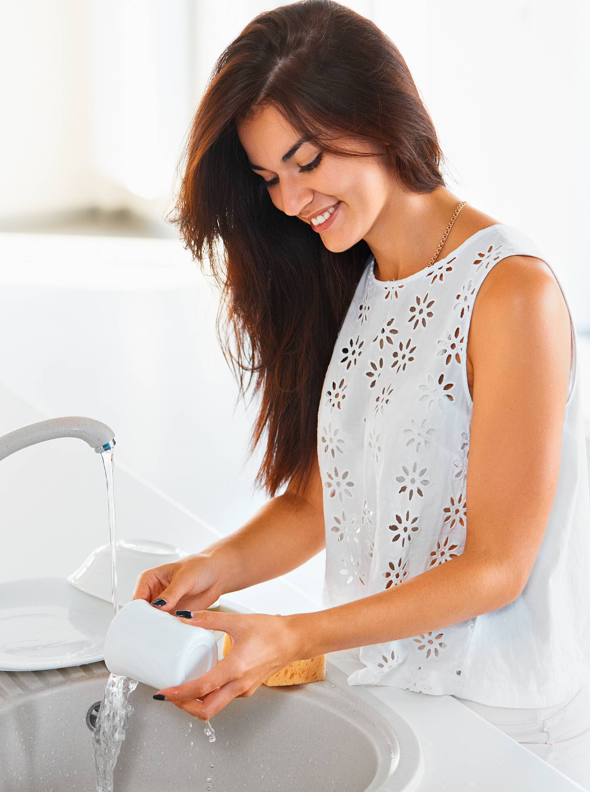 Woman washing a cup in white kitchen. Vegetables