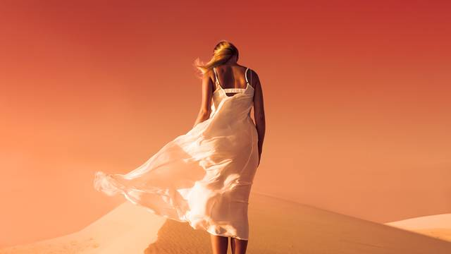 Woman in fluttering dress. Desert and sand dunes. Red sky. Mars.