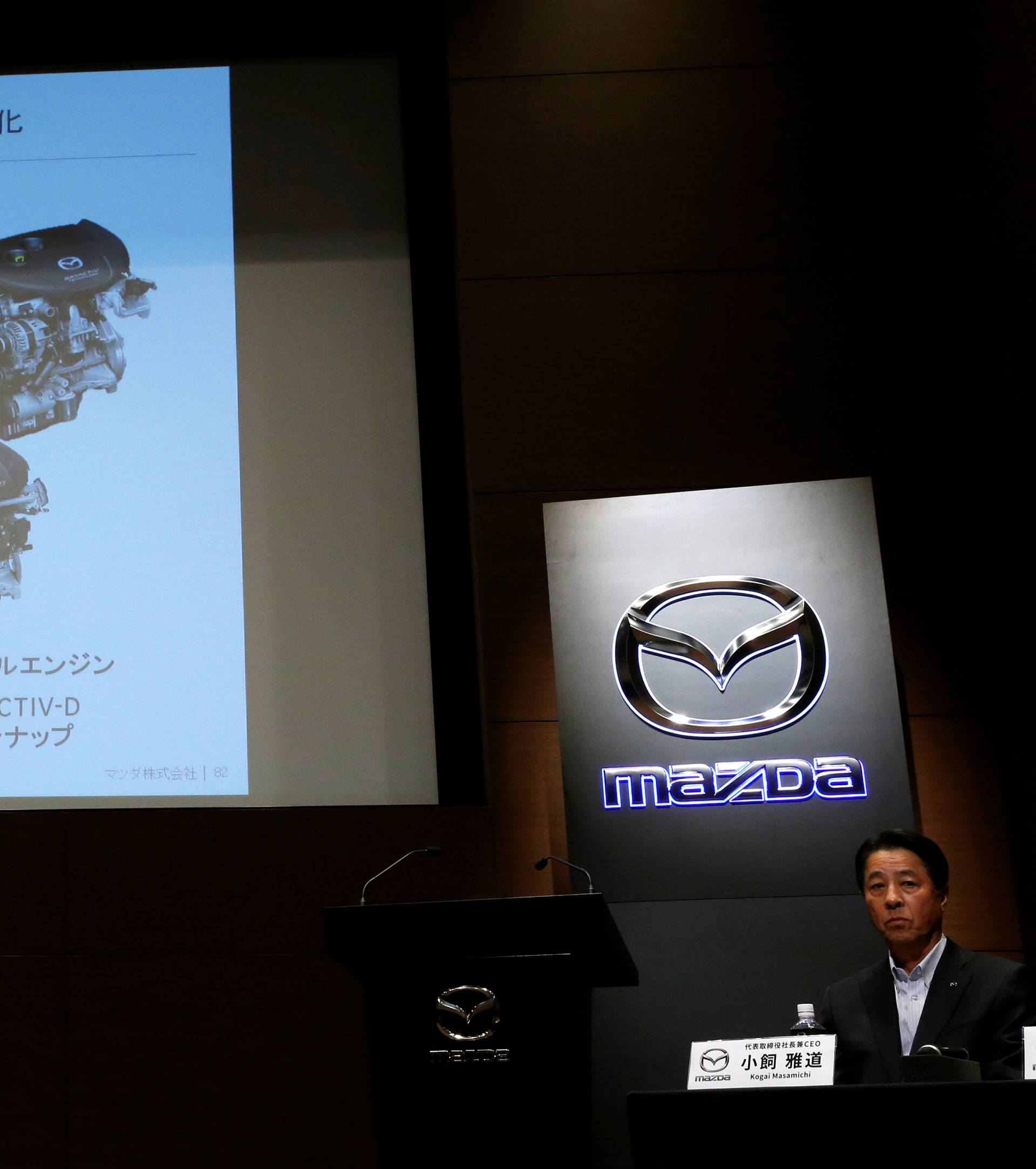 Mazda Motor President Masamichi Kogai sits next to a screen showing a slide about its new engine, to be called SKYACTIV-X, at a news conference in Tokyo
