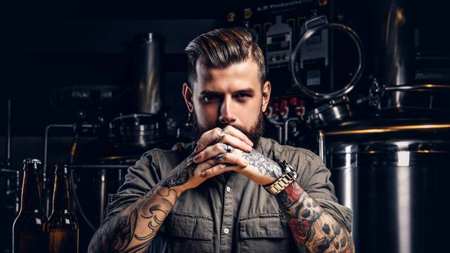 Portrait of a pensive tattooed hipster male with stylish beard and hair in the shirt in indie brewery.