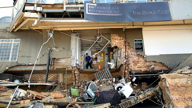 A man stands inside an area of The Beach Club after it was damaged by severe weather, which brought strong winds and heavy rain to the east coast of Australia, at Collaroy beach in Sydney