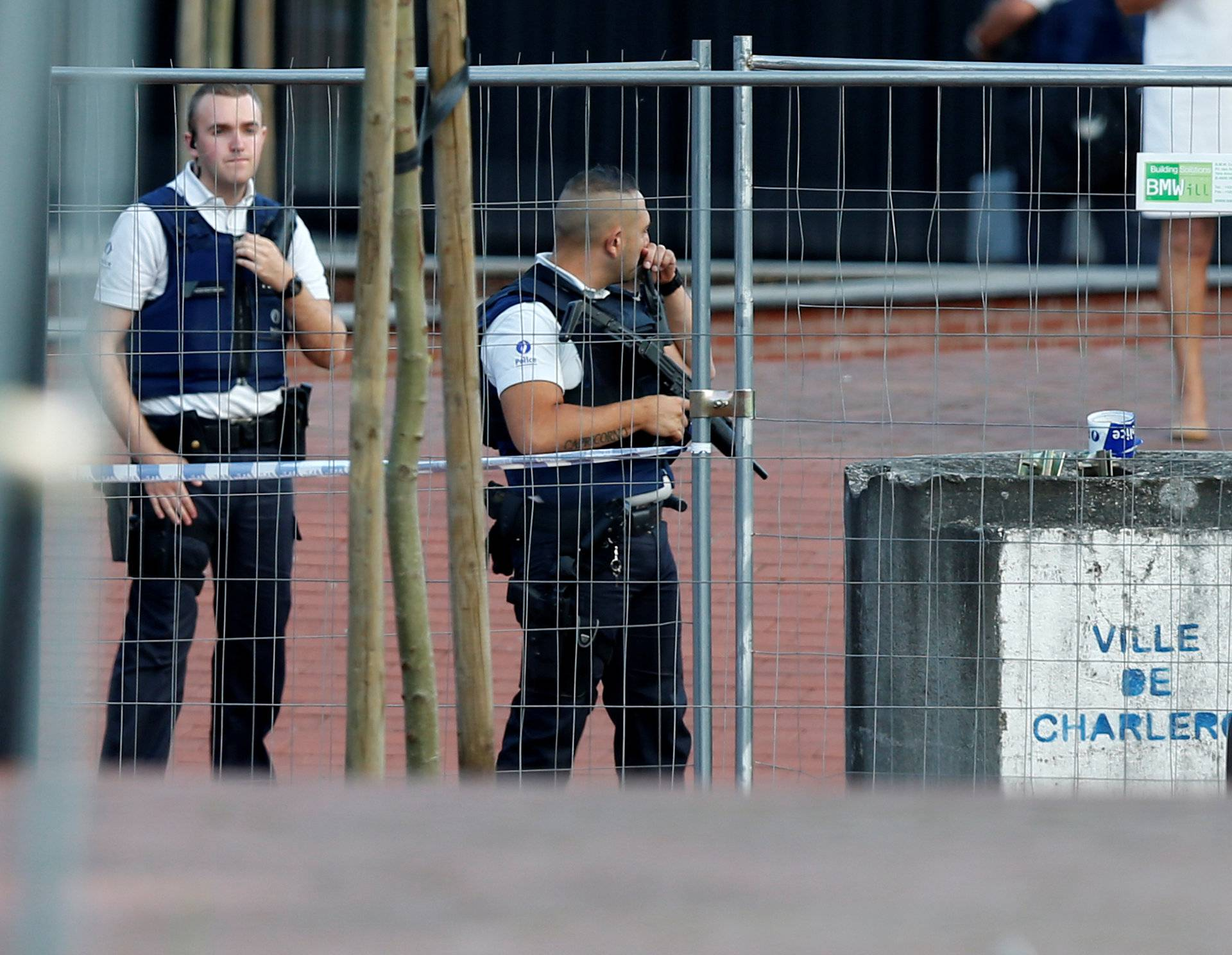 Belgian police officers stand guard outside the main police station after a machete-wielding man injured two female police officers before being shot in Charleroi