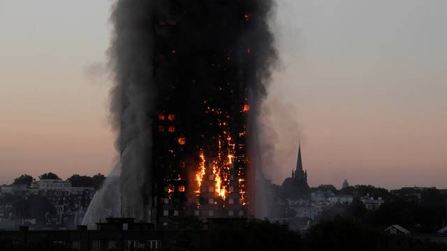Flames and smoke billow as firefighters deal with a serious fire in the Grenfell Tower apartment block at Latimer Road in West London
