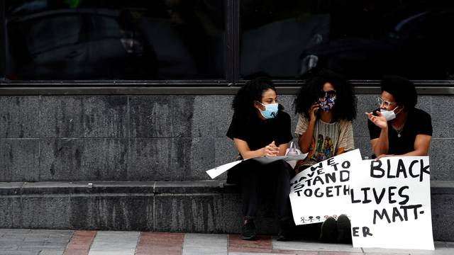 Women talk during a protest against racial inequality and call for defunding of Seattle police, in Seattle downtown