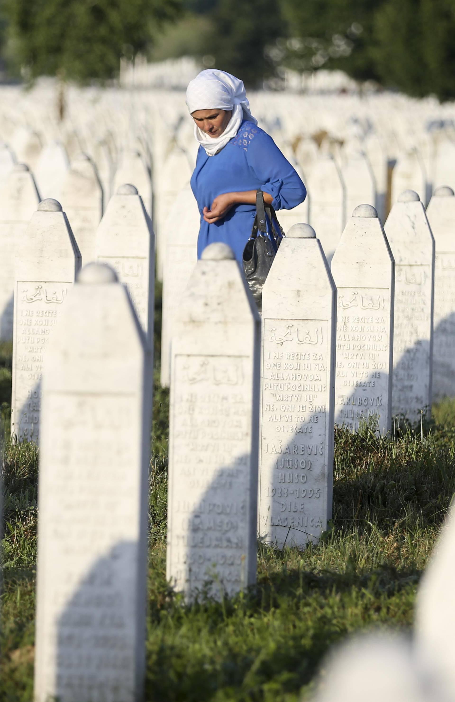 A woman walks among graves in Memorial Center Potocari, near Srebrenica